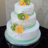 Claire's Wedding Cake Round Wedding cake with peach and green accents. Fondant accents with gumpaste flowers.