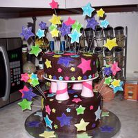Shooting Stars This was a vanilla cake iced in chocolate ganache. The stars are made of fondant and covered with colored sugar. Before the fondant dried...