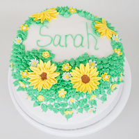 Flowered Birthday Cake 4 layer yellow cake with sliced strawberries and homemade strawberry glaze filling. Vanilla buttercream with fondant flowers.