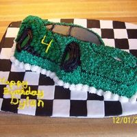 100_2361S.jpg Wilton Lightning McQueen cake done as a NASCAR racing car with fondant checkerboard squares