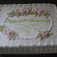 Anniversary This is an 11x15 sheet cake with pink royal icing roses. The rest is buttercream with a little glitter sprinkled on top!