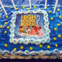 High School Musical 9x13 cake decorated with buttercream and blue sparkle gel. The picture is the laminated CD cover.