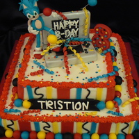"Tristion's Sonic Cake  This is a one layer 12"" chocolate and one layer 8"" white. Frosted and filled with buttercream. All accents are candy clay. Sonic..."
