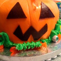 Pumpkin pumpkin cake made from a bundt pan covered in MMF with buttercream grass and store bought candies.