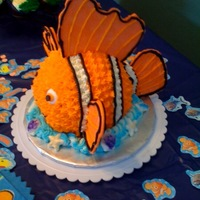 Nemo Cake Used a small ball pan to create Nemo. Fins are made from tinted white chocolate and the cake is covered in buttercream.