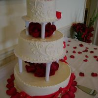 December Wedding red velvet cake w/rasberry filling and BC w/fondant swags and roses.Fresh roses through the centers.