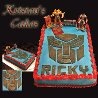 Transformers Cake Transformers logo, childs name and age made out of fondant. Transformers figures and cube are toys.