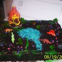 Dinosaur Land!! This cake is all edible but the dinosaurs themselves. I mad the volcano out of chocolate and the little bushes out of fruit roll ups. The...