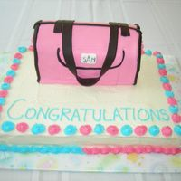 Diaper Bag Cake   This is a WASC cake with a replica of a Dooney & Bourke diaper bag on top. Diaper bag is covered with fondant.