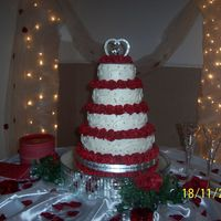 White Buttercream With Red Roses This is my first wedding cake for my sister's wedding. It is all buttercream with edible silver pearl accents.