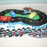 Cars Race Track Made for my son's 5th birthday. 1/2 sheet cake, cut into a figure '8' . Made with buttercream frosting. Letters and grass...