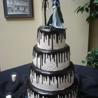 Corpse Bride Wedding Cake Four tier buttercream cake with black fudge ooze dripping from each tier. The Corpse Bride and her Groom top the cake.