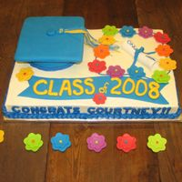 Courtney's Graduation This was an Aloha-themed graduation cake. 1/2 white and 1/2 chocolate cake with b/c icing. Fondant cap, tassle, diploma and flowers.