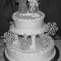 "Snowflake Wedding Cake 10"" and 6"" cakes iced in buttercream. White sparkles around snowlike edges. Snowman and snowmam are Christmas ornaments (I added..."