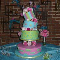 Topsy Turvey Love This cake is covered with brightly colored fondant with a variety of patterns. There are gumpaste hearts with edible pictures of the bride...