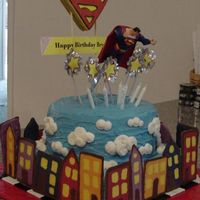 Up, Up, And Away! This is a double round layer on top of a square, iced in buttercream. The clouds are piped on. Buildings are made from candy melts. The...