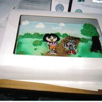 Dora And Boots Dora and Boots are BCT. The sky and grass are airbrushed with piped buttercream accents. Trees and bushes are also piped buttercream. The...