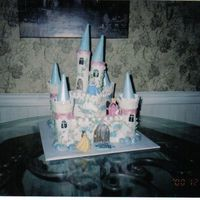 Cinderella Castle Cake This took forever to make! The castle is white cake with cookie filling covered with buttercream. The turrets are fondant with icecream...