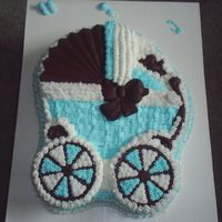 Baby Shower Cake Baby shower cake made of buttercream icing, solid chocolate hood, bow, bird and wheels.