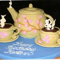 "Tea Pot Tea pot is made with the sports ball pan, cups are cup cakes. Covered in fondant with fondant flowers and white chocolate ""steam&quot..."