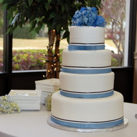 New Year's Eve Wedding Cake  Satinice white fondant with ribbon detail - periwinkle shimmer and black satin. Silk hydrangeas on top. Vanilla Bean cake with pineapple...