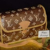 Lv Purse  Iced in buttercream with a sugarpaste strap/closure. The logo was 'painted' on with a mixture of melted cocoa butter and petal...
