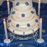 My First Wedding Cake!  I made this for a royal blue themed winter wedding. The flowers are fondant with buttercream center dots. The cakes are covered with...