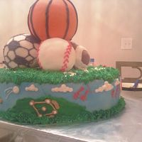 "Sports double layer 12 "" yellow cake with buttercream icing rice cereal shaped sports balls covered in fondant scenes for each sport along..."