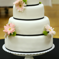 4 Tier Daisy Wedding Cake 4 tier (6-9-12-14) white fondant wedding cake decorated with black grossgrain ribbon and fresh pale pink gerber daisies. I couldn't...