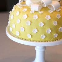 Yellow & White Round Fondant Cake Yellow round fondant cake with quilt pattern and small white flowers and bow on milkglass cake stand