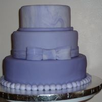 Purple Fondant Tiered Cake This is a sample cake I did for an upcoming Wedding demonstration. All three cakes are styrofoam. The bottom is a medium purple, the middle...