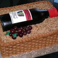 Wine Bottle In Basket 50/50 wine bottle with edible image label on buttercream basketweave cake with coconut filler.