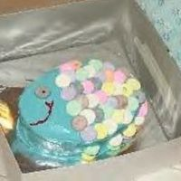My Daughter's First Cake :) My 9 year old daughter made this fish cake for her dad last week for his birthday. It is white cake with bc frosting. The scales are Necco...