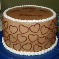 Chocolate Anniversary  8 inch round with chocolate buttercream. Hearts on the side were made with an impression from a cookie cutter. The top says Happy 25th...