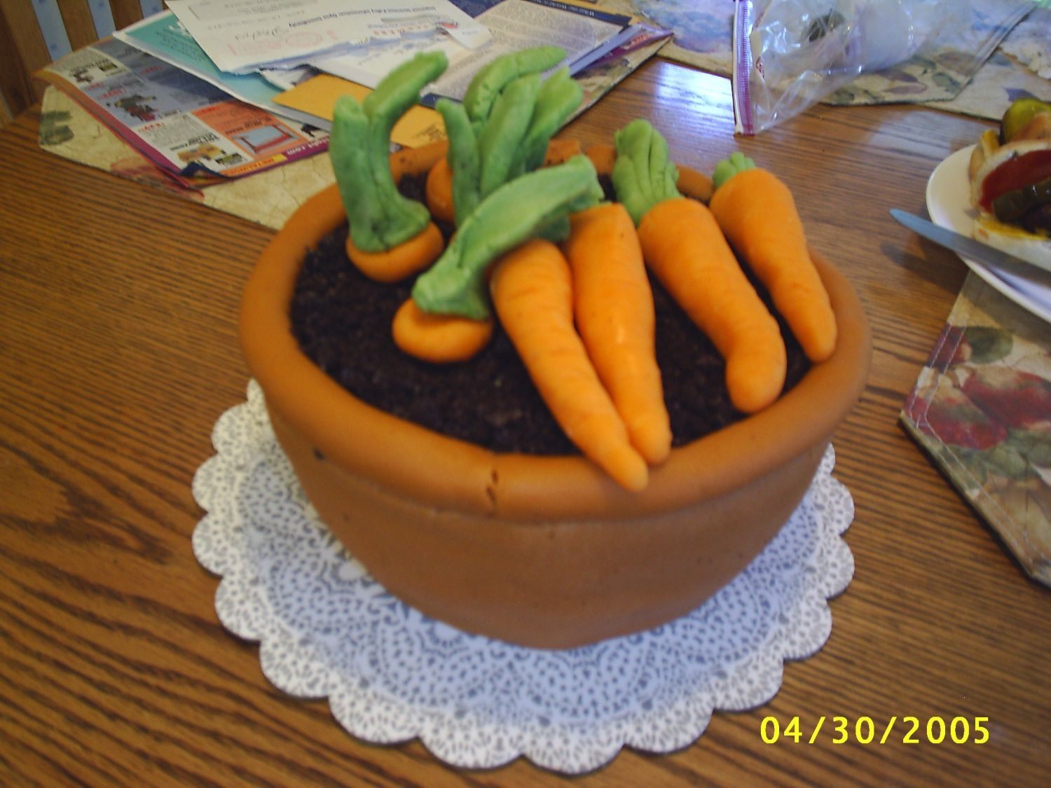 Pot Of Carrots Pot and carrots are marizpan. Dirt is crushed oreos. Cake was sculpted from round layer cake.