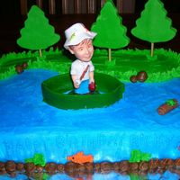 Fisherman 1/4 sheet cake. Devils food with buttercream dream icing. Fisherman was a bobble head. I made the trees, boat and log with the turtle out...