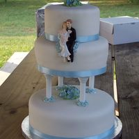 First Wedding Cake White cake covered in fondant. The flowers on top and in the middle are royal icing petunias and the flowers around the columns are blue...