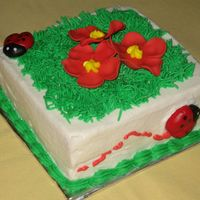 Ladybug And Flowers 4 in. white cake with BC. Ladybugs and flowers are fondant. This was the child's personal cake that went with the large ladybug cake...