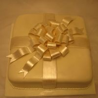 Present With Big Bow This was for a 40th birthday. The customer wanted an elegant cake for the birthday girl. White fondant with a gumpaste bow dusted in pearl...