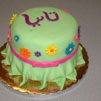 Dress Cake This was for a girl who loves Gerber daisies, and she's also half Egyptian. She wears a necklace with her name in Arabic, which is on...