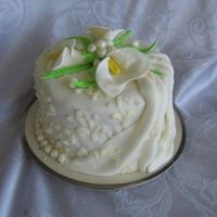 Calla Lily Cake Almond cake filled with raspberry and apricot preserves, covered in almond buttercream and marshmallow fondant. The pearls and drapes are...