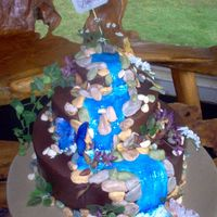 Waterfall Cake  Cake was for a special church function. 2.5 tiers stacked, iced with choco bc icing, rocks are fondant, foliage/flowers are silk,...