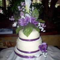 Wedding In Purples yellow cake iced with BC covered with fondant, BC accent dots and silk ribbon on sides. The bride wanted a large/tall floral arrangement (...