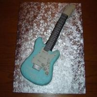 Guitar Cake My first attempt at sculpting a cake. The picture is misleading -- this cake is very small. The gentleman was turning 18 and wanting a...