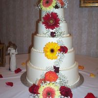 Merchant Wedding This 5-tier wedding cake is covered in buttercream and accented with fresh flowers.