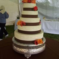Brown Ribbon This 5-tier wedding cake is covered in buttercream and accented with real brown ribbon and fresh flowers.