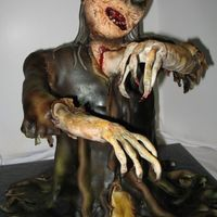 Zombie Cake This cake has an internal pvc support. The body is about 7 layers of cake, and the head is rice krispie treats.