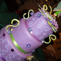 Peter Pan Neverland Tinkerbell Birthday Cake 4 teir purple Tinkerbell cake with jewels. Top three teirs are dummy, gumpaste flower petals.