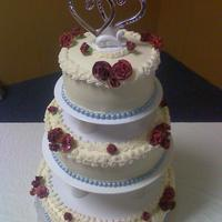 Betty's Cake Round BC covered cake decorated with silver sixlets for the border and burgandy gumpaste carnations