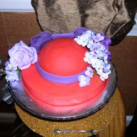 Red Hat Cake The flowers are actually silk flowers, but the hat and bow are all fondant. I made it for a Red Hat party at my mom's house